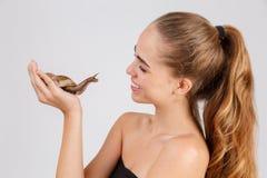 Młodej dziewczyny chwyty na palmie i spojrzenia przy ślimaczkiem Ahatina Odizolowywający na bielu Zdjęcie Royalty Free