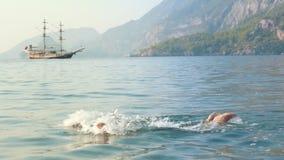 Młodej dziewczyny dopłynięcie w morzu Dziecka doskakiwanie w morze z starym statkiem na tle zdjęcie wideo