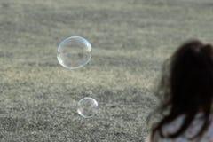 Młodej dziewczyny dopatrywania bąble unoszą się i latają w powietrzu fotografia stock