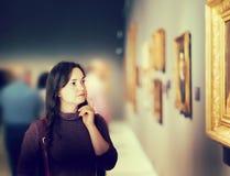 Młodej dziewczyny dopatrywanie przy kolekci sztuki wystawą Obrazy Stock