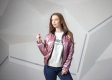 Młodej dziewczyny dziewczyna jest ubranym kurtkę z terenem dla twój logo w górę białej kobiety hoodie, obraz royalty free