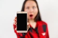 Młodej dziewczyny kobieta w czerwieni i czerni koszula trzyma smartphone z pustym czerń ekranem pionowo przed ona obrazy stock