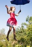 Młodej dziewczyny latanie na niebie z parasolem w jej ręce obraz stock