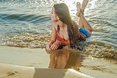 Młodej dziewczyny lying on the beach na plażowy patrzeć daleko od obrazy royalty free