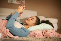 Młodej dziewczyny lying on the beach na podłoga i śpiewa mądrze telefon Przestrzeń dla kopii zdjęcia royalty free