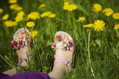 Młodej dziewczyny lying on the beach na trawie po środku dandelions w świetle słonecznym z malującymi palec u nogi gwoździami Zdjęcia Stock