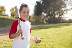 Młodej dziewczyny mienia kija bejsbolowego i baseballa spojrzenia kamera zdjęcia stock