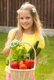 Młodej dziewczyny mienia kosz warzywa i patrzeć kamerę Zdjęcia Royalty Free