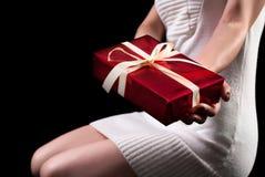 Młodej dziewczyny mienia prezenta czerwony pudełko z łękiem Obrazy Stock