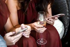 Młodej dziewczyny mienia smartphone i wskazywać przy partyjnym świętowaniem, patrzejący parawanowym i pije szampanem zdjęcia royalty free