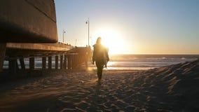 Młodej dziewczyny mienia surfboard na plaży Kobiety odprowadzenie z kipielą ocean Piękny zmierzch, wiatr dmucha, piasek zbiory wideo
