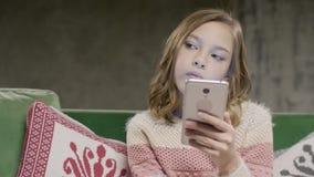 Młodej dziewczyny mienia telefon w rękach siedzi w pokoju zdjęcie wideo