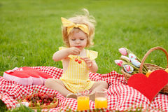 Młodej dziewczyny mienia wiśnie siedzi na koc Zdjęcie Royalty Free