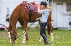 Młodej dziewczyny narządzania koń dla przejażdżki Zdjęcia Stock