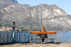 Młodej dziewczyny obsiadanie na ławce patrzeje jezioro i góry Obraz Stock