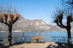 Młodej dziewczyny obsiadanie na ławce patrzeje jezioro i góry Obrazy Stock