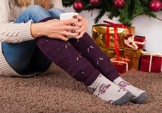 Młodej dziewczyny obsiadanie na dywanowej podłoga, mienia filiżance kawy w rękach na nogach z i choinki i prezenta pudełkami w pó fotografia stock