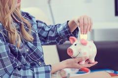 Młodej dziewczyny obsiadanie na leżanki i kładzenia litecoin w piggybank zdjęcie royalty free