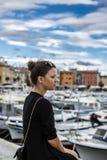 Młodej dziewczyny obsiadanie na molu blisko portu morskiego Piękna dziewczyna na tle łodzie, miasto i jaskrawi nieba, Obrazy Stock