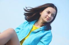 Młodej dziewczyny obsiadanie na nieba backgraund w lecie zdjęcia stock