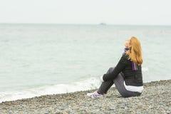 Młodej dziewczyny obsiadanie na otoczak plaży denną twarzą denny popiół na chmurnym dniu Zdjęcie Royalty Free