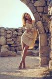 Młodej dziewczyny obsiadanie na plaży po zmierzchu w dennym tle Zdjęcie Royalty Free