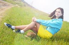 Młodej dziewczyny obsiadanie na polu w lecie zdjęcia royalty free