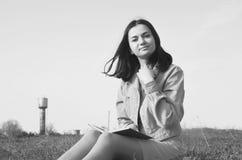 Młodej dziewczyny obsiadanie na polu z książką w lecie zdjęcie stock