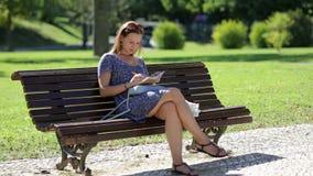 Młodej dziewczyny obsiadanie przy ławką w parku i