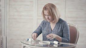 Młodej dziewczyny obsiadanie przy stołem i robić ` Dreamcatcher ` zdjęcie wideo
