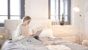 Młodej Dziewczyny obsiadanie w łóżku i działaniu na laptopie zbiory