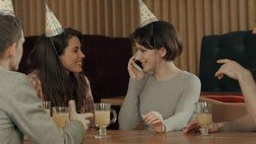 Młodej dziewczyny odświętności urodziny w kawiarni, opowiada na telefonie komórkowym Obrazy Royalty Free