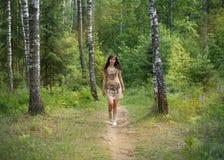 Młodej dziewczyny odprowadzenie wzdłuż ścieżki w lasowym parku obrazy royalty free