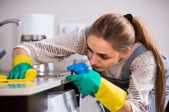 Młodej dziewczyny okurzanie ukazuje się w mieszkaniowej kuchni zdjęcia stock