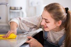 Młodej dziewczyny okurzanie ukazuje się w mieszkaniowej kuchni obraz royalty free