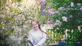 Młodej dziewczyny podlewania wiśnia na tle bez, letni dzień zdjęcie wideo