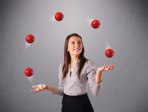 Młodej dziewczyny pozycja i żonglować z czerwonymi piłkami obraz stock