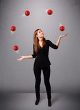 Młodej dziewczyny pozycja i żonglować z czerwonymi piłkami Zdjęcia Stock