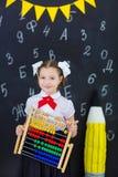 Młodej dziewczyny pozycja przed chalkboard ściana z cegieł z listami na nim jest ubranym mundurek szkolnego z ogromnego pensil żó zdjęcie stock