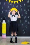 Młodej dziewczyny pozycja przed chalkboard ściana z cegieł z listami na nim jest ubranym mundurek szkolnego z ogromnego pensil żó obrazy royalty free