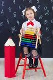 Młodej dziewczyny pozycja przed chalkboard ściana z cegieł z listami na nim jest ubranym mundurek szkolnego z ogromnego pensil żó zdjęcie royalty free