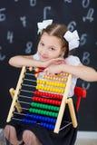 Młodej dziewczyny pozycja przed chalkboard ściana z cegieł z listami na nim jest ubranym mundurek szkolnego z ogromnego pensil żó fotografia stock