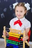 Młodej dziewczyny pozycja przed chalkboard ściana z cegieł z listami na nim jest ubranym mundurek szkolnego z ogromnego pensil żó fotografia royalty free