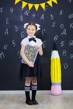 Młodej dziewczyny pozycja przed chalkboard ściana z cegieł z listami na nim jest ubranym mundurek szkolnego z ogromnego pensil żó zdjęcia royalty free