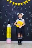 Młodej dziewczyny pozycja przed chalkboard ściana z cegieł z listami na nim jest ubranym mundurek szkolnego z ogromnego pensil żó obraz stock