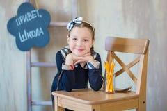 Młodej dziewczyny pozycja przed chalkboard ściana z cegieł z listami na nim jest ubranym mundurek szkolnego z ogromnego pensil żó obrazy stock