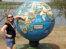 Młodej dziewczyny pozycja przed gigantyczną światową kulą ziemską Uganda Zdjęcia Stock