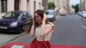 Młodej dziewczyny słuchająca muzyka w hełmofonach na opustoszałej ulicie zbiory wideo