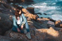 Młodej dziewczyny samotny obsiadanie na skałach morzem w zrelaksowanej pozie zdjęcie stock
