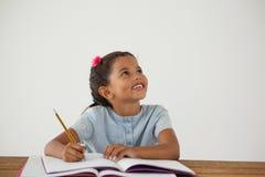 Młodej dziewczyny writing w jej książce przeciw białemu tłu Zdjęcia Stock
